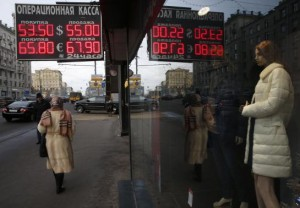 People walk along a street past a board showing currency exchange rates in Moscow
