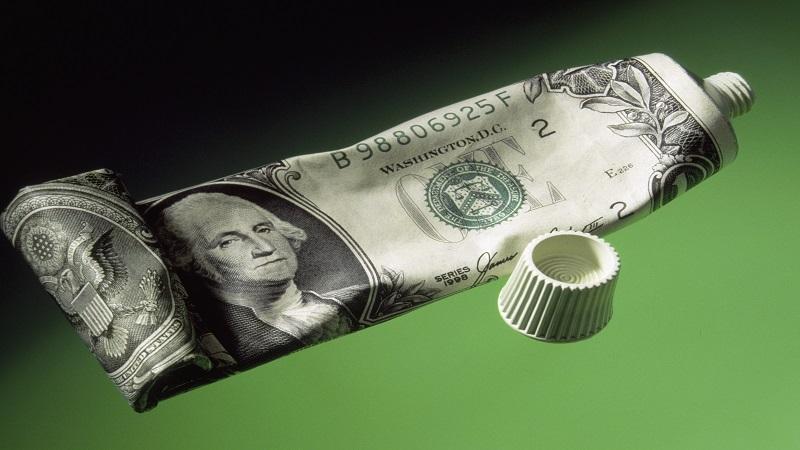 US dollar wrapped onto toothpaste tube